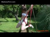 Sexy young whore in nylons and an adult baby diaper bound in a swing