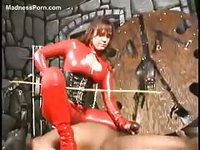 Dominating redhead babe in red skin tight PVC punishing a bound stud