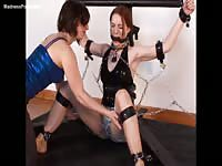 Long-legged teen slut with red hair in BDSM restraints helpless while a female teases her cunt