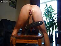 Muscled Spanish daddy rides on a huge dildo as fast as he can